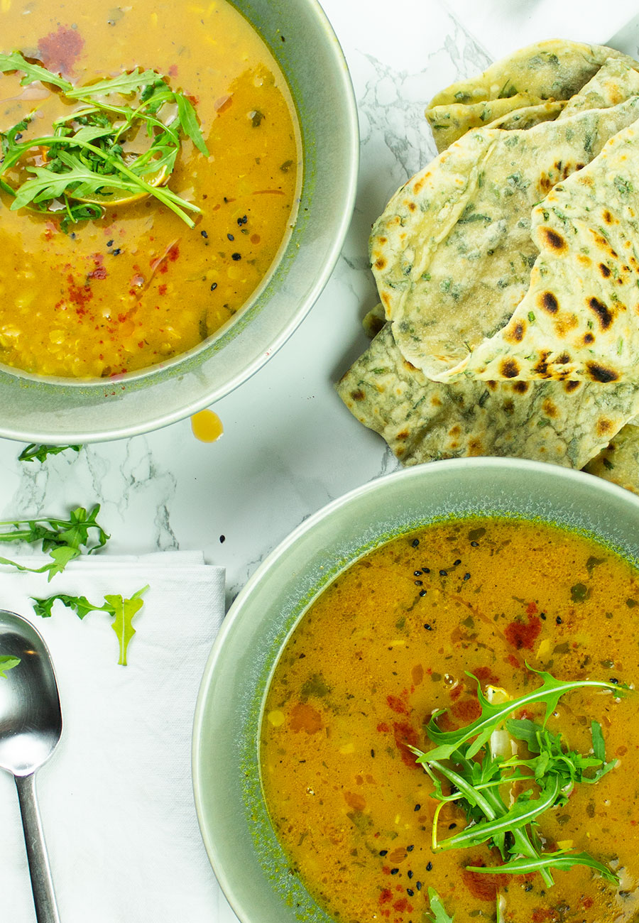 Hearty Indian dahl red lentil soup in bowls with flatbreads on the side