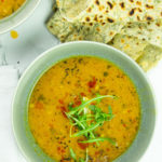 Tasty red lentil soup in a bowl with flatbreads