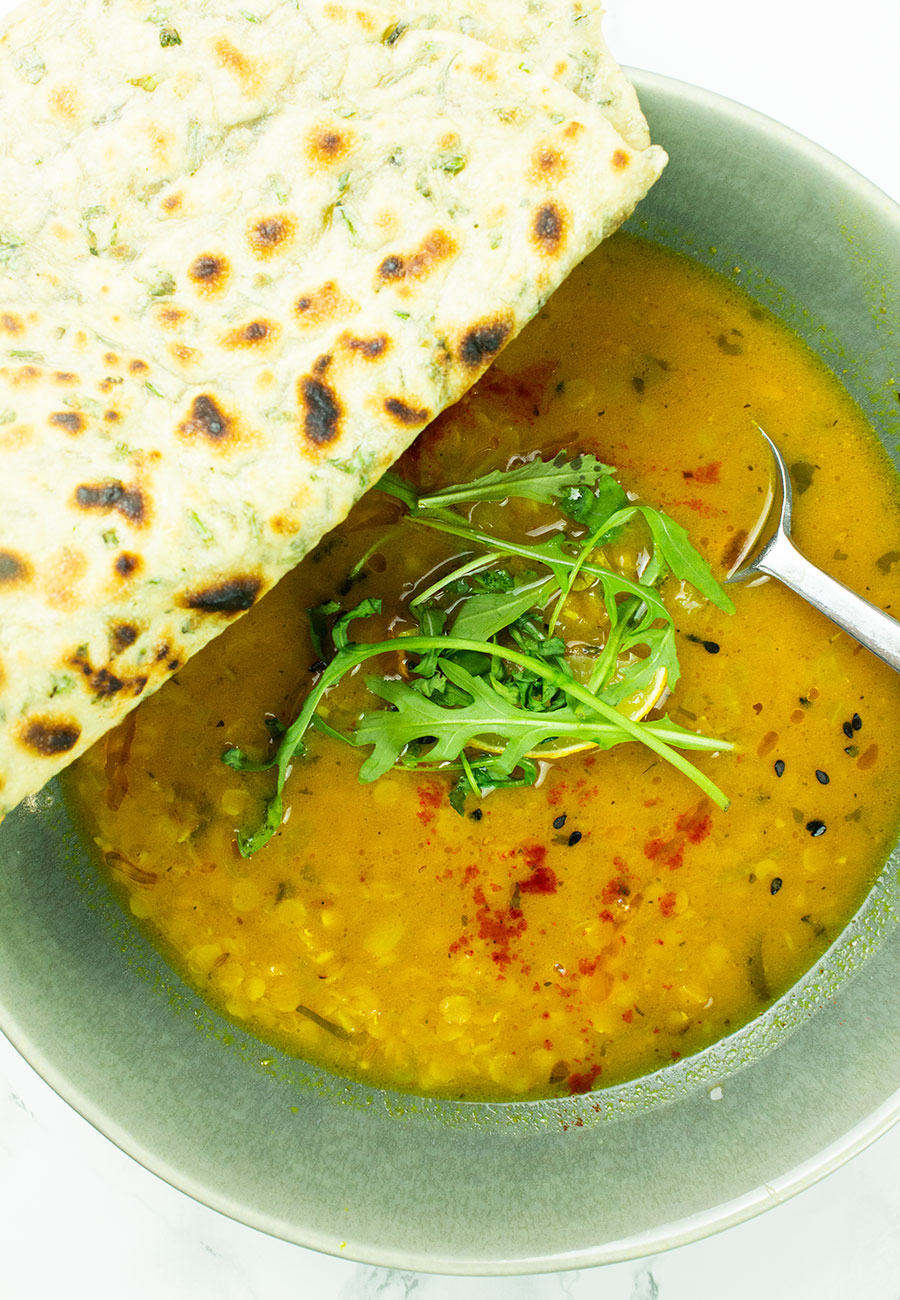 Dahl soup in a bowl with flatbreads on top of the bowl