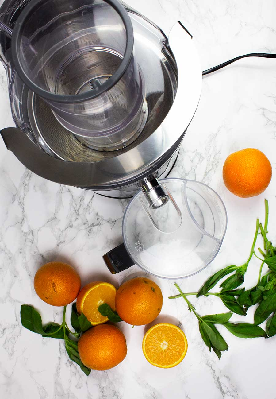 Juicer and oranges with basil